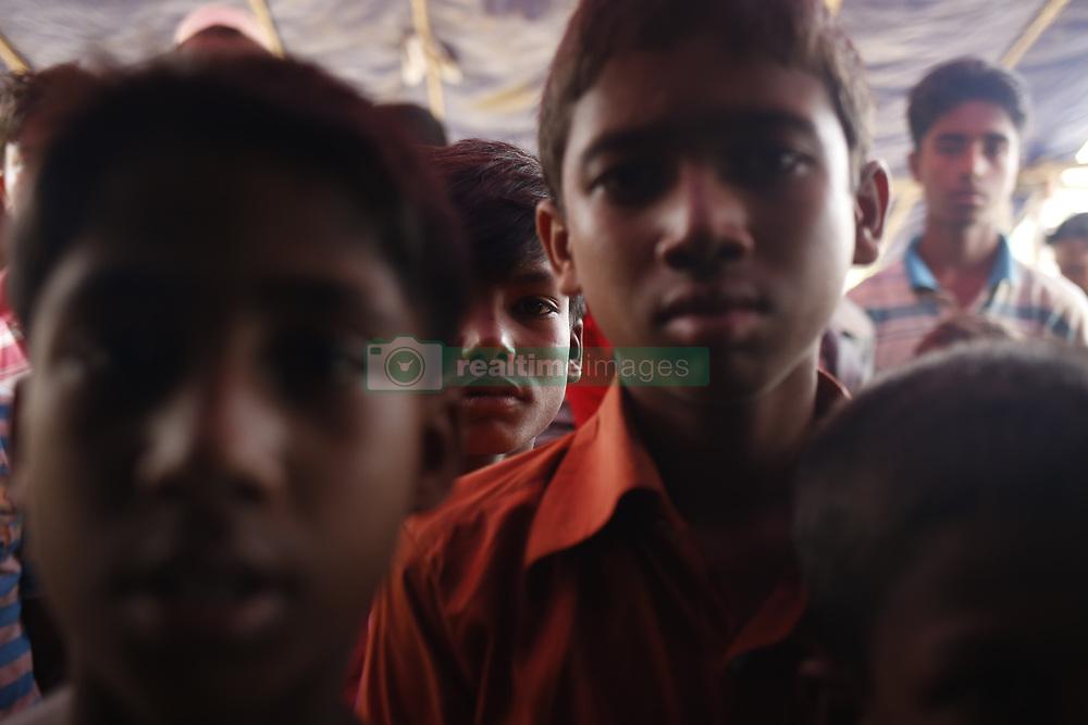 September 9, 2017 - Teknaf, Bangladesh - Rohingya refugee boys wait for food near Balukhali refugee camp after crossing the Bangladesh-myanmar border in Ukhia..Rohingya refugee walks muddy path after crossing the Bangladesh- Myanmar border, in Teknaf. (Credit Image: © Md. Mehedi Hasan/Pacific Press via ZUMA Wire)