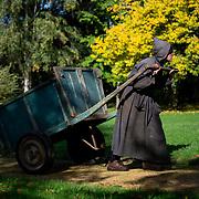 A monk pulls his cart in the abbey park. He is carrying soil for his plantations. Solesmes on 18-10-19<br /> Un moine tire sa charrette dans le parc de l'abbaye. Il transporte du terreau pour ses plantations. Solesmes le 18-10-19