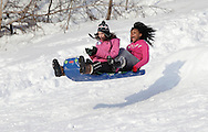 Central Valley, NY - Two teenage girls fly through the air after riding off a jump built on  a hill next to the Central Valley Elementary School after a snow storm on  Feb. 27, 2010.