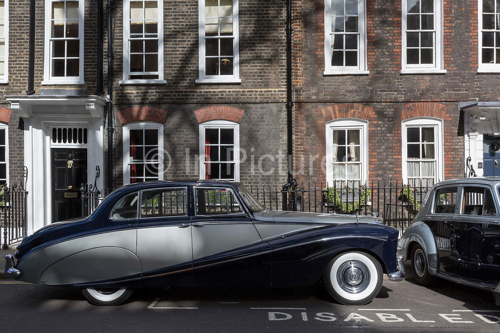 A 1964 Empress Bentley and a 1954 Rolls-Royce Silver Dawn are parked in Smith Square, a small square behind the Houses of Parliament, before collecting their VIP passengers - barristers who are being sworn in as QCs aka Silks in legal vernacular, on 11th March 2019, in London, England.
