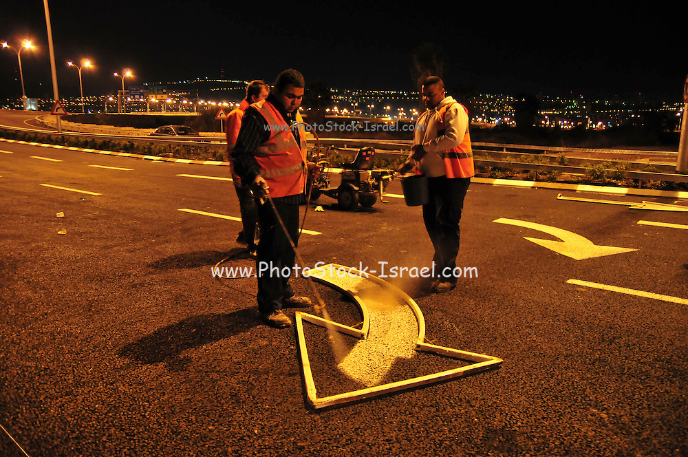 Workers paint road markings at night sprinkling reflective glass dust