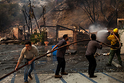 November 10, 2018 - Malibu, California - Garner Gerson, left, pulls a water hose helping to extinguish hot spots after a structure burnt to the ground along the Pacific Coast Highway. The Woolsey fire doubled in size overnight with 70,000 acres burned forcing nearly 95,000 residents to evacuate their homes in Los Angeles and Ventura counties as of Saturday morning according to Cal Fire. (Credit Image: © Joel Angel Juarez/ZUMA Wire)