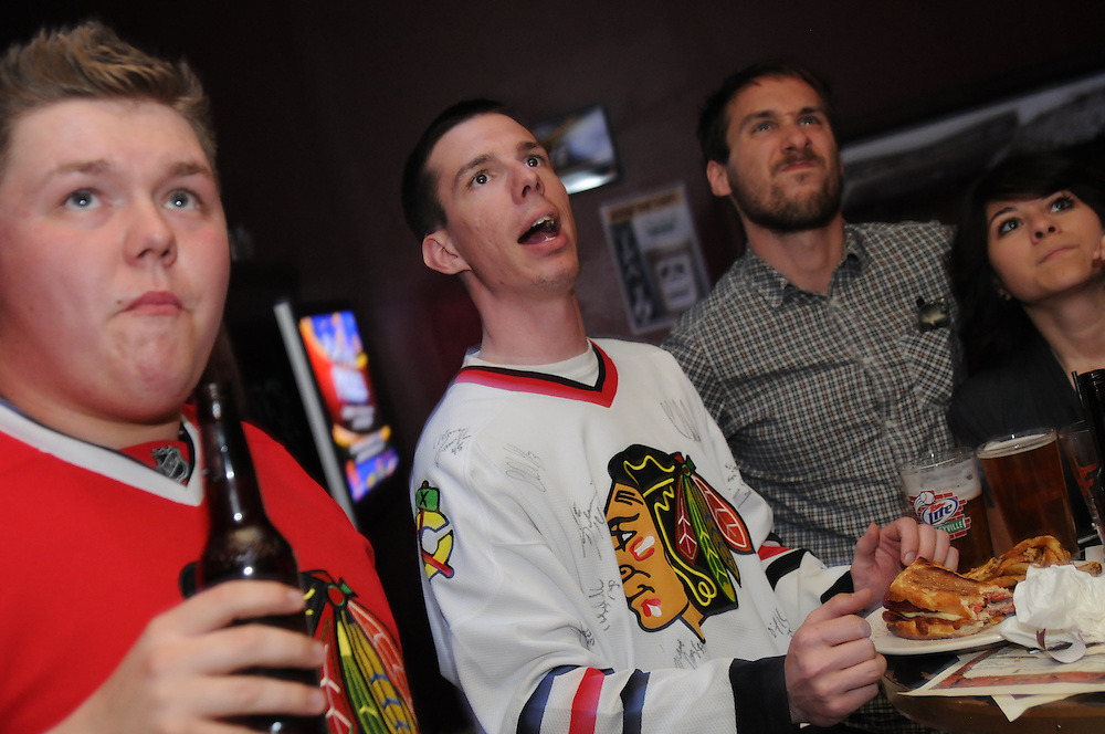 Chicago Blackhawks fans (l to r) DJ Harrell, Matt Rosenbaum, Jerald Cizmadja, and Vicky Leos watch their away team take on the Vancouver Canucks in the Stanley Cup Playoff Semifinals at Red Ivy bar, an official Hawks Roadwatch location in Chicago.