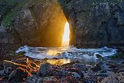Sunlight shines through a sea arch at Harris Beach on the Southern Oregon Coast near Brookings.