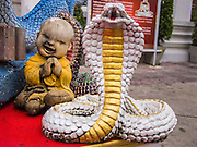 16 NOVEMBER 2013 - BANGKOK, THAILAND: A statue of a cobra guards a statue of the baby Buddha at Wat Saket in Bangkok. Wat Saket is on a man-made hill in the historic section of Bangkok. The temple has golden spire that is 260 feet high which was the highest point in Bangkok for more than 100 years. The temple construction began in the 1800s in the reign of King Rama III and was completed in the reign of King Rama IV. The annual temple fair is held on the 12th lunar month, for nine days around the November full moon. During the fair a red cloth (reminiscent of a monk's robe) is placed around the Golden Mount while the temple grounds hosts Thai traditional theatre, food stalls and traditional shows.     PHOTO BY JACK KURTZ