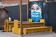Street art mural of a Muslim woman wearing an NHS face mask in a deserted outdoor bar in Borough as the national coronavirus lockdown three continues on 3rd March 2021 in London, United Kingdom. With the roadmap for coming out of the lockdown has been laid out, this nationwide lockdown continues to advise all citizens to follow the message to stay at home, protect the NHS and save lives, and the streets of the capital are quiet and empty of normal numbers of people.