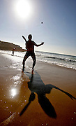 Portuguese Summer. A man plays beach tennis at Praia das Maçãs beach in Sintra.