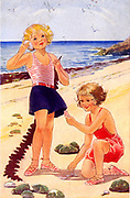 Girls playing with shells on a sandy beach on their seaside holiday. English postcard c1940.