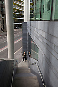 A lady changes her shows at the bootom of some steps on Upper Thames Street (upstream from London Bridge) in the City of London - the capital's financial district, on 11th October 2018, in London, England.