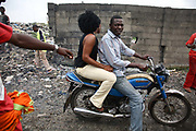 Alaba International Market. A couple is passing by on a motor bike down a lane covered with crushed CRT glass. The nearby rubbish dump where  old printer circuit boards, old TV casings and lots of CRT glass can be forund lying around.<br /> New and old - and a lot of non-working electronic goods such as TVs and computers come in to the market via Lagos harbour from the US, Western Europe and China. This picture is part of an undercover investigation by Greenpeace and Sky News.  A TV-set originally delivered to a municipality-run collecting point in UK for discarded electronic products was tracked and monitored by Greenpeace using a combination of GPS, GSM, and an onboard radiofrequency transmitter placed inside the TV-set.  The TV arrived in Lagos in container no 4629416 and was found in Alaba International Market and bought back by Greenpeace activist. The TV was subsequently brought back to England and used as proof of illegal export of electronic waste. A number of individual are currently on trial in London in connection with illegal exports(Nov 2011)
