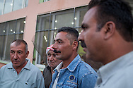 Fawaz Subhi, 37 second from right and his fellow residents from Kobane/Ayn al-Arab in Syria at their new temporary shelter in a former wedding hall in the Turkish town of Suruç