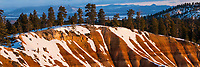 First light of the day strikes the canyon rim of Bryce Canyon National Park as the Winter snow clings to the cliff face.