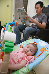 Chinese father reading with his baby daughter
