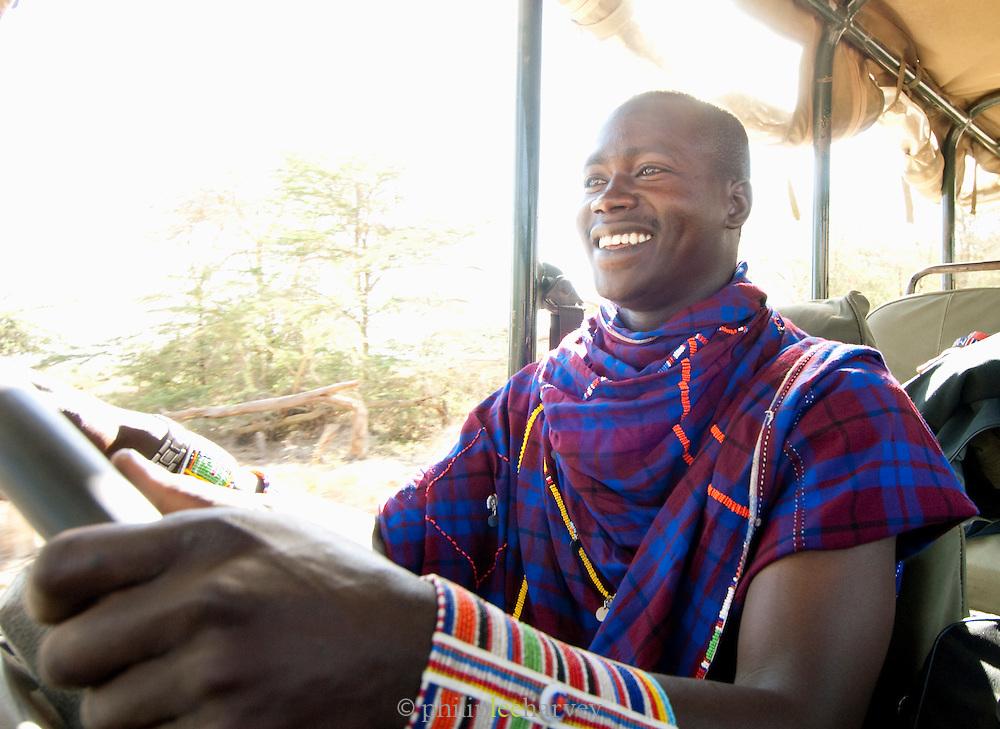 Maasai tribesman working as guide and driver on eco tourism safari, Amboseli National Park, Kenya