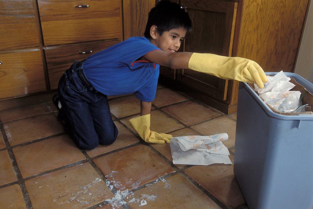 Hispanic boy, age 10, cleans up broken glass.  Model Release.<br /> ©Bob Daemmrich
