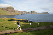 A woman walking at Neist Point in Glendale on the 4th September 2016 on the Isle of Skye in Scotland in the United Kingdom. Neist Point is the most Westerly point on the Isle of Skye with views over Moonen Bay to Waterstein Head.