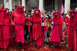 London, UK. 27th August, 2021. Members of the Extinction Rebellion Red Rebel Brigade take part in a mass civil disobedience involving the spreading of fake blood in Paternoster Square following a Blood Money March through the City of London on the fifth day of Impossible Rebellion protests. Extinction Rebellion were intending to highlight financial institutions funding fossil fuel projects, especially in the Global South, as well as law firms and institutions which facilitate them, whilst calling on the UK government to cease all new fossil fuel investment with immediate effect.