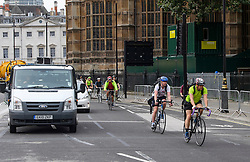 © London News Pictures. 25/08/2016. Cyclists ignore the cycle lane and chose to join moving traffic while using a cycle lane on Abingdon Street, approaching Parliament Square. Cyclists repeatedly ignore new cycle lanes installed around westminster in central London. Between the hours of 8am and 9am on Wednesday 24/08/2016, 266 (two hundred and sixty six) cyclists passed through the red light at one of the newly installed  bike lanes and only 15 (fifteen) cyclists stopped.  The light system is designed to allow either vehicles or cyclists to pass at one time in order to make the junction safer for cyclists..... **VIDEO AVAILABLE** Photo credit: London News Pictures.
