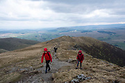 Hikers walk up a steep rugged dirt path of Doddick Fell on Blencathra Fell in Lake District National Park, Cumbria, UK. The hill is also known as Saddleback and is one of the most northerly hills in the Lake District. The sky is full of clouds.