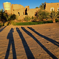 Africa, Morocco, Skoura. Long shadows of four photographers photographing kasbah ruins in Skoura.