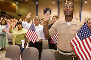 July 4, 2008 -- Phoenix, AZ: KERBY TEKEMAQUE (LEFT) a member of the US Marines originally from Haiti, takes the oath of citizenship at a naturalization ceremony in Phoenix, AZ, Friday. He is shipping out with his unit to Iraq next week and said he wanted to deploy as a US citizen. About 300 people from 41 countries were naturalized as US citizens at South Mountain Community College, in Phoenix, AZ, Friday. It was the 20th year the college has hosted the Fiesta of Independence. More than 5,000 people have become naturalized US citizens at the Fiesta of Independence. More than 5,000 people have become naturalized US citizens at the Fiesta of Independence. The largest number of new citizens, 158, came from Mexico. There were also large numbers of new citizens from the Philippines, Bosnia-Herzegovnia and India.  Photo by Jack Kurtz