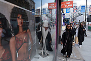 A cultural clash as young women in fully covered clothes pass an underwear shop and scantily dressed models look out from pictures in the shop window as some non-essential shops re-open, shoppers return to Oxford Street while social distancing measures are put in place by the various retail shops which are open on 26th June 2020 in London, England, United Kingdom. As the July deadline approaces and government will relax its lockdown rules further, the West End remains quiet, apart from this popular shopping district, which itself has far fewer people on its pavements than normal.