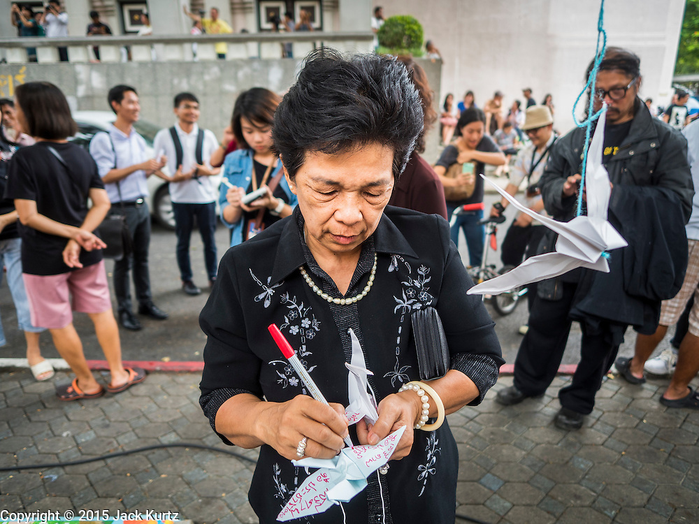 """06 JULY 2015 - BANGKOK, THAILAND: A person hangs a paper dove during a protest called """"Wing of Peace"""" at Thammasat University/ More than 100 people gathered at Thammasat University in Bangkok Monday to show support for 14 students arrested two weeks ago. The students were arrested for violating orders against political assembly. They face criminal trial in military courts. The students' supporters are putting up """"Post It"""" notes around Bangkok and college campuses up country calling for the students' release.      PHOTO BY JACK KURTZ"""