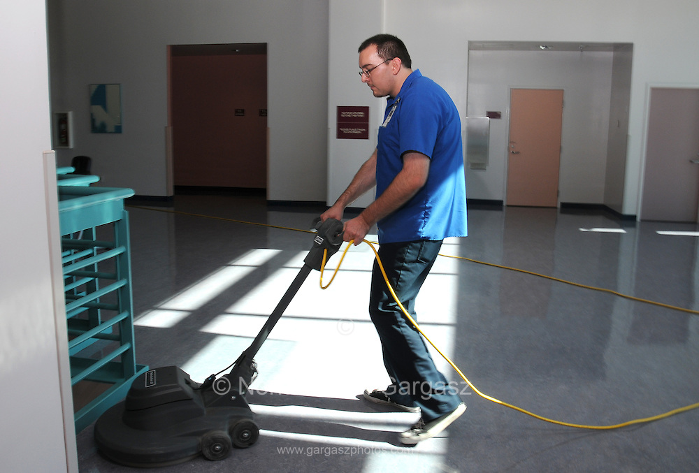 Andrew Cervantez, employee of the Custodial Facilities Management, buffs the floor at the Student Recreation Center, University of Arizona, Tucson, Arizona, USA.