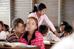 Teacher Ms. Invanh assists children in her class in a school where AusAid has funded training for minority group teachers, Ban Dakduang, Dakcheung, near Sekong, Lao PDR