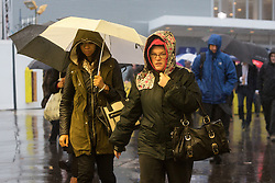 © Licensed to London News Pictures. 21/10/2014. London, UK. Commuters leave London Bridge station during heavy rain and wind in the City of London this morning, 21st October 2014 after the end of Hurricane Gonzalo reached the UK overnight. Photo credit : Vickie Flores/LNP