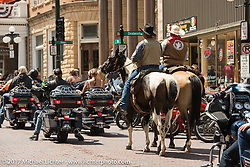 Cowboys ride their horses up Main Street in Deadwood amongst all the bikers during the annual Sturgis Black Hills Motorcycle Rally. SD, USA. Monday August 7, 2017. Photography ©2017 Michael Lichter.