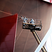 shipyard workers spray paiting a ship red in Dubai