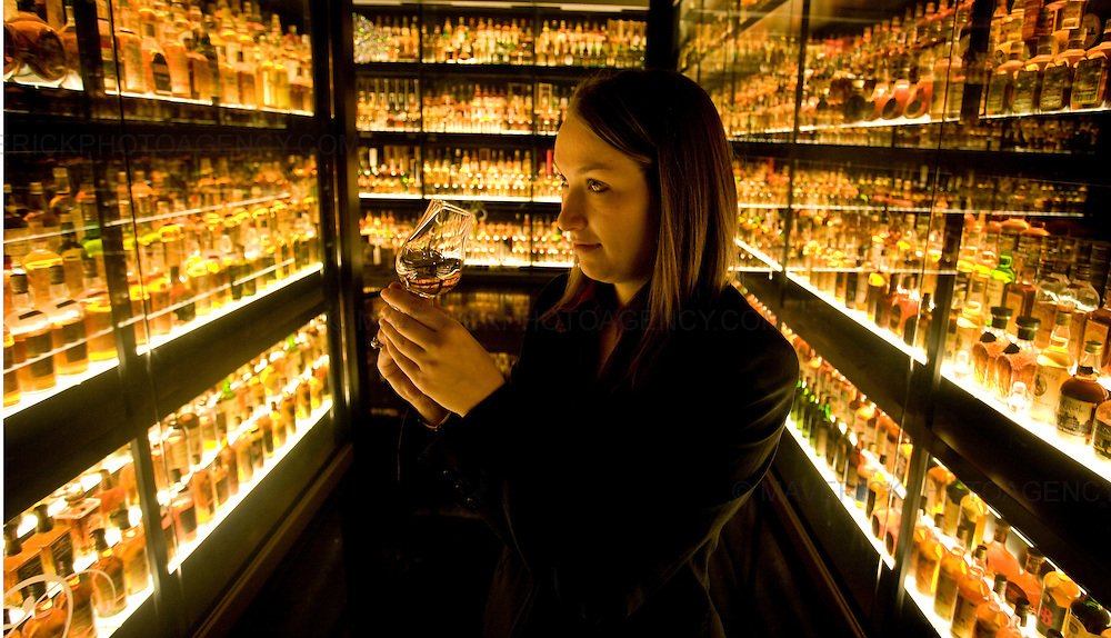 A women examines  Whisky bottles at  the newly refurbished Scottish Whisky Experience centre vault which is home to the Diageo Claive Vidiz Scotch Whisky Collection. Featuring 3,384 bottles, the collection  is the largest in the world.