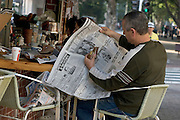 A man reading the news during a coffee break in Tel Aviv, Israel