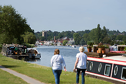 © Licensed to London News Pictures. 15/06/2021. Henley-on-Thames, UK. Two women walk along the bank of the River Thames at Henley-on-Thames in Oxfordshire on a hot summer's morning. Photo credit: Ben Cawthra/LNP