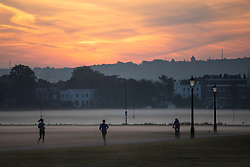 © Licensed to London News Pictures. 22/09/2021. London, UK. Members of the public exercise during sunrise on a misty morning on Blackheath Common in South East London. Temperatures are expected to rise with highs of 22 degrees forecasted for parts of London and South East England today . Photo credit: George Cracknell Wright/LNP