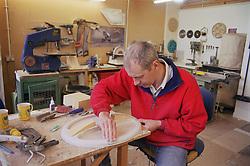 Model maker at work in workshop sanding mould,