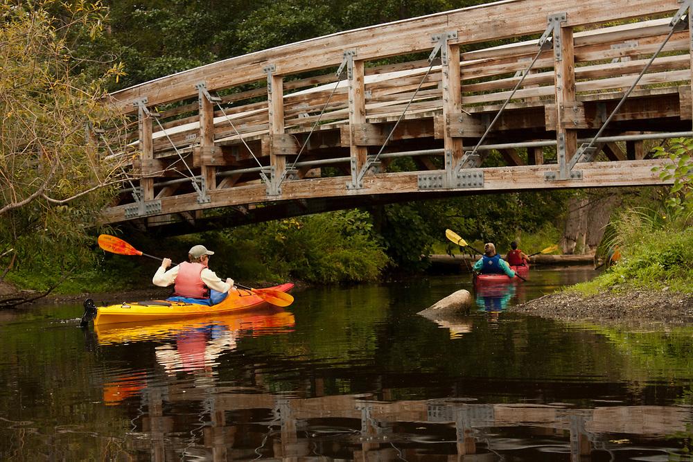 United States, Washington, Seattle. People paddle sea kayaks under a footbridge on Lake Washington near the Arboretum.