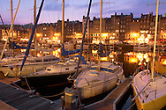 Nigh harbour scene with yaughts and harbour restaurants. Honfleur, Normandy, France. . Honfleur is especially known for its old port, characterised by its houses with slate-covered frontages, painted many times by artists, including in particular Gustave Courbet, Eugène Boudin, Claude Monet and Johan Jongkind, forming the école de Honfleur (Honfleur school) which contributed to the appearance of the Impressionist movement. .<br /> <br /> Visit our FRANCE HISTORIC PLACES PHOTO COLLECTIONS for more photos to download or buy as wall art prints https://funkystock.photoshelter.com/gallery-collection/Pictures-Images-of-France-Photos-of-French-Historic-Landmark-Sites/C0000pDRcOaIqj8E