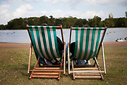 Two people of green and white striped deck chairs sit facing a small lake in Kensington Palace Gardens, London.