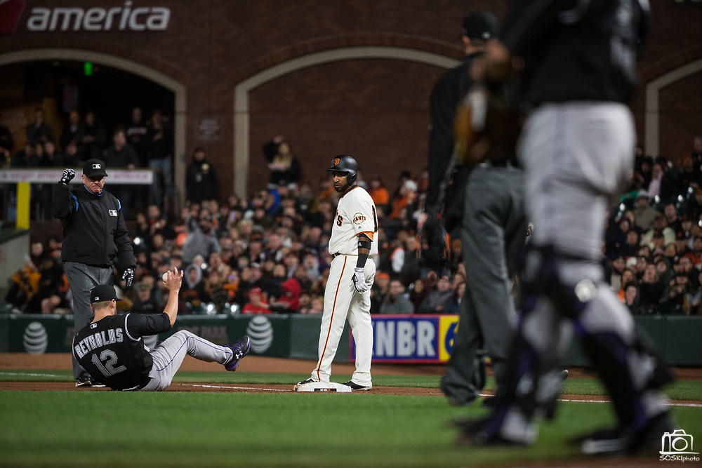 Colorado Rockies first baseman Mark Reynolds (12) makes a diving catch at first base to get San Francisco Giants shortstop Eduardo Nunez (10) out at AT&T Park in San Francisco, California, on April 14, 2017. (Stan Olszewski/Special to S.F. Examiner)