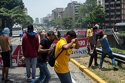 April 4, 2017 - Caracas, Venezuela - Opposers to Nicolas Maduro's government clash with security forces during a demonstration in Caracas, today April 4, 2017. Protesters clashed with police in Venezuela Tuesday as the opposition mobilized against moves to tighten President Nicolas Maduro's grip on power. Protesters hurled stones at riot police who fired tear gas as they blocked the demonstrators from advancing through central Caracas, where pro-government activists were also planning to march. (Credit Image: © Manaure Quintero/NurPhoto via ZUMA Press)