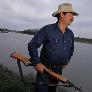 Bud Natus is a rancher whose property borders Mexico along the Rio Grande river in Eagle Pass, Texas. Natus carries a rifle for protection against migrant and drug smugglers. Please contact Todd Bigelow directly with your licensing requests.