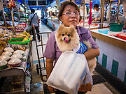 18 JULY 2013 - BANGKOK, THAILAND:  A woman through the Onnuch (also known as On Nut) Wet Market off of Sukhumvit Soi 77 in Bangkok with her pet dog.       PHOTO BY JACK KURTZ