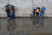 Families shelter beneath umbrellas during a sudden downpour in Trafalgar Square, on 13th August 2018, in London, England.