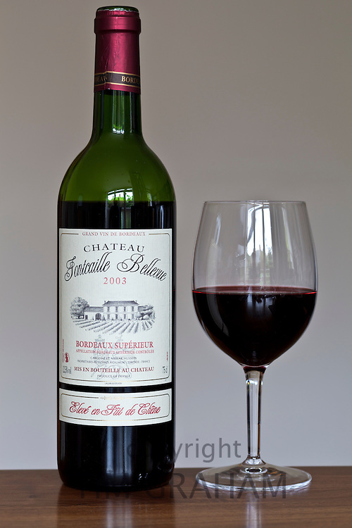 Bottle of French Bordeaux wine, Chateau Fontcaille Bellevue 2003 Grand Vin de Bordeaux and poured glass of wine,  France