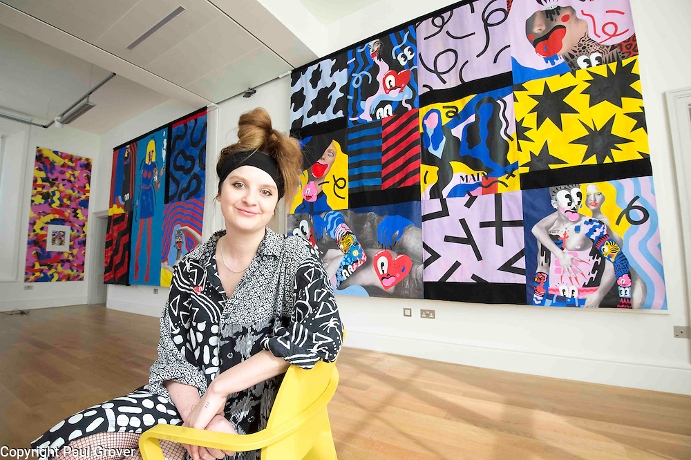 London based,Colchester Born artist/illustrator Hattie Stewart with her work at The House of Illustration at King's Cross for her exhibition On 17 April 2015 Hattie Stewart: Adversary. This is a new body of work from the self-proclaimed professional 'doodle-bomber', in which Stewart takes on glossy advertising imagery with her characteristic homage-meets-satire approach.<br /> Hattie Stewart: Adversary is the first in House of Illustration's series of illustrator commissions – new work from contemporary illustrators to be shown in House of Illustration's South Gallery.