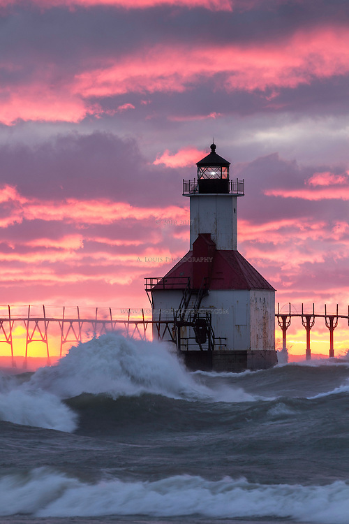 The setting sun paints the clouds over St. Joseph's lighthouse in fiery shades of crimson