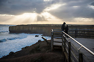 A couple stands together just before sunset at the London Bridge (Arch) overlook at Port Campbell National Park on the Great Ocean Road, Australia