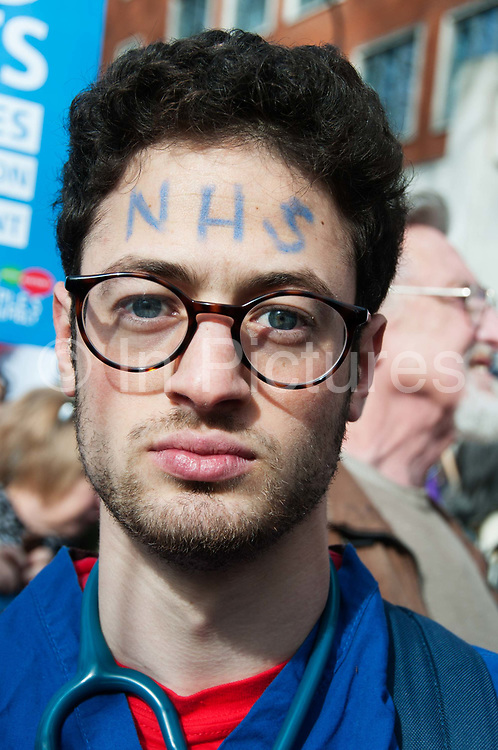 Tens of thousands of health workers, activists and members of the public protested against austerity and cuts in the NHS National Health Service on March 4th 2017 in London, United Kingdom. A student doctor wearing blue scrubs has a stethoscope around his neck and the words NHS written on his forehead.